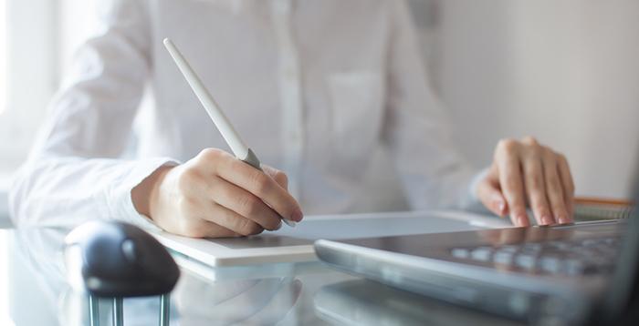Female designer using graphics pad in office